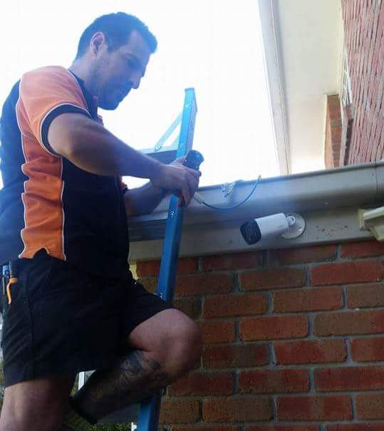 electrician on top of ladder installing camera in melbourne home